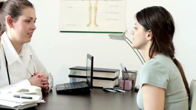Young smiling doctor talking to her female patient video