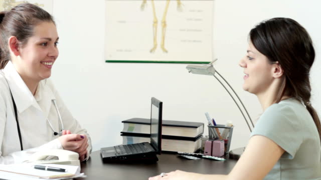 Young smiling doctor talking to her patient at office video
