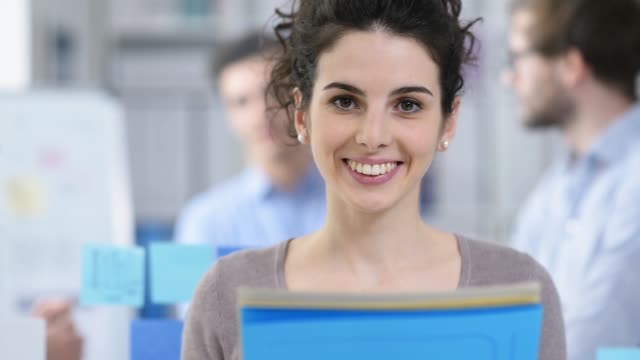 young smiling female office worker in the office - apprendista video stock e b–roll