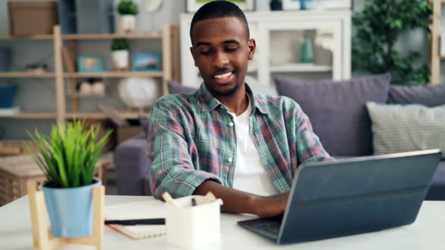 Young  smiling freelancer is working at home using laptop computer