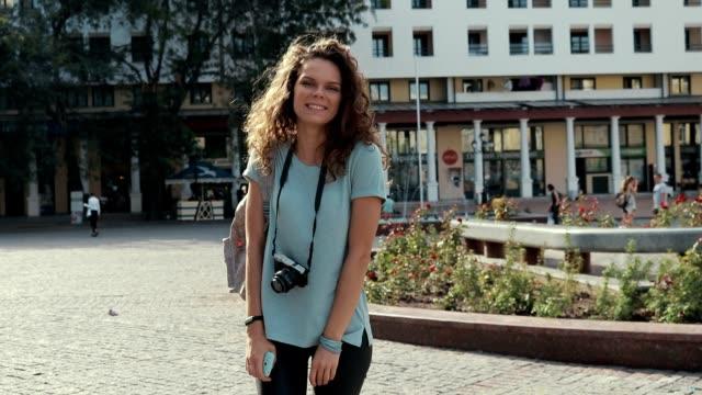stockvideo's en b-roll-footage met jonge glimlachende meisje met fotocamera wandelen in de stad in de zomer - curly brown hair