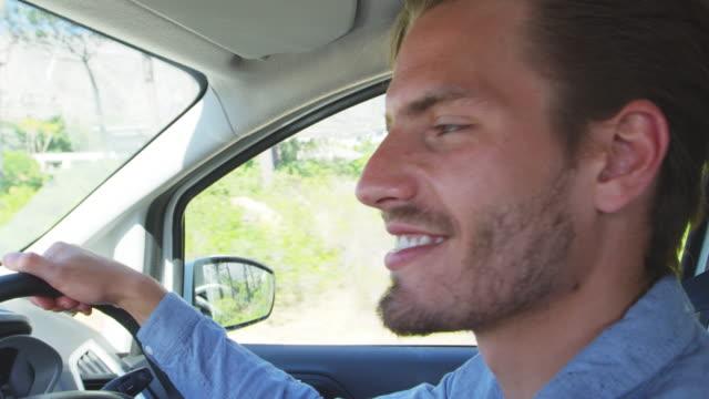 道路の旅行に、車を運転して笑みを浮かべて青年 - 運転手点の映像素材/bロール