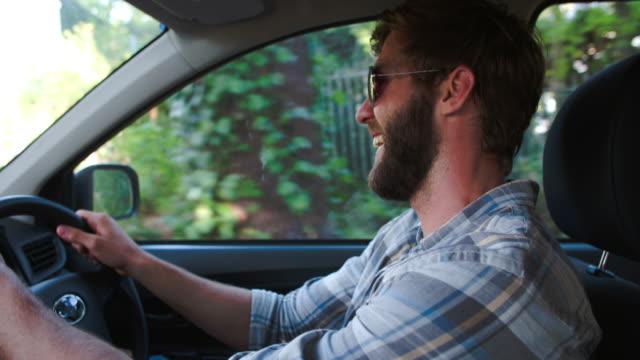 持って笑う若い男性のお車、フロントの乗客席からの眺め ビデオ