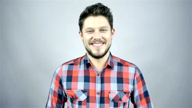 Young smiling man in a checkered shirt in studio video