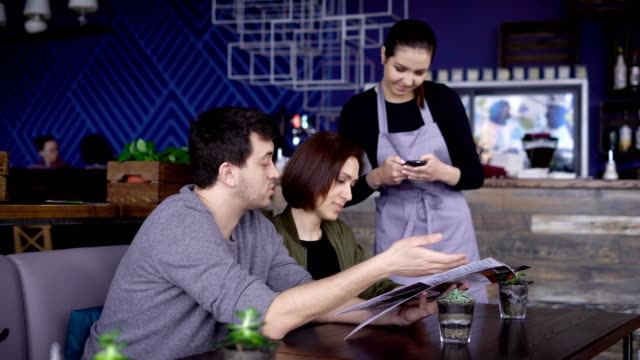 Young smiling waitress standing in cafe near the table of happy couple and putting their order into digital tablet. Man and woman in the restaurant are celebrating their anniversary and choosing dishes video