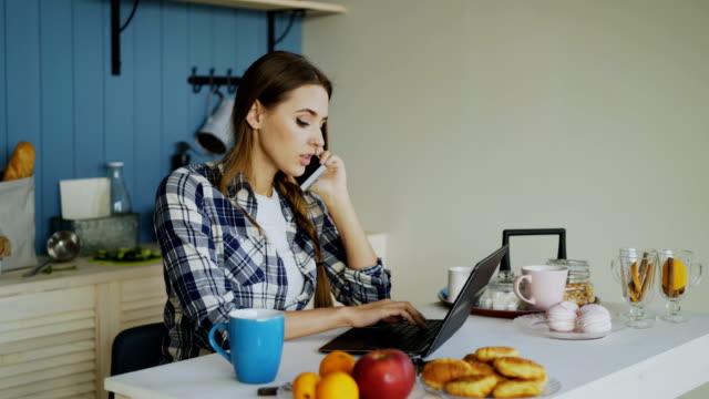 vídeos de stock, filmes e b-roll de jovem mulher sorridente navegação social media usando o computador portátil e telefone a falar durante o café da manhã - no telefone