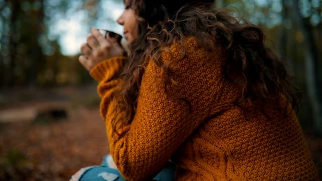 vídeos de stock, filmes e b-roll de jovem mulher sorridente, apreciando na bebida quente em floresta - outono