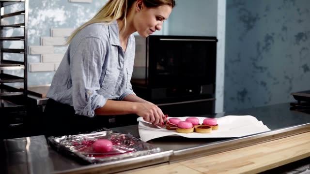 vidéos et rushes de jeune souriant en chemise bleue et tablier noir sur une phase finale de préparation français dessert - mettre le gâteau glacé rose dans tartles. cuisine moderne. boulangerie, pâtisserie, concept culinaire - boulanger