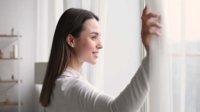 Young smiling woman opening curtain looking through window
