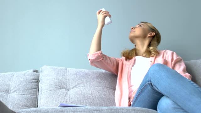 ung leende kvinna som slår på luftkonditioneringen och känner sig avslappnad, svalare - kvinna ventilationssystem bildbanksvideor och videomaterial från bakom kulisserna