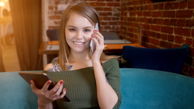 young smiling women having video conversation using smartphone in coffee shop - banchi scuola video stock e b–roll
