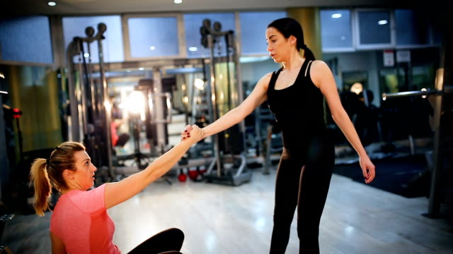 young smiling women stretching together while holding hands - donna forzuta video stock e b–roll