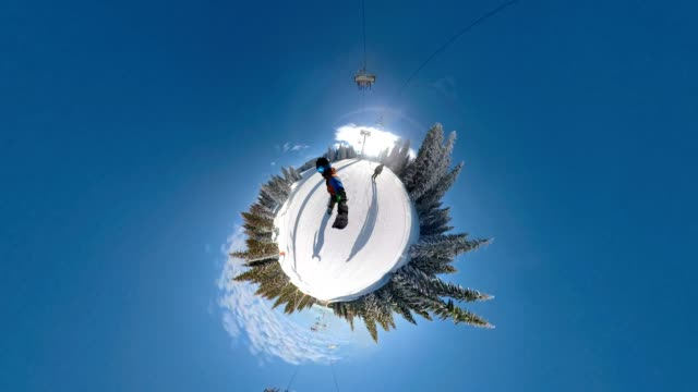 young snowboarder enjoying his ride in a ski resort - fish eye video stock e b–roll