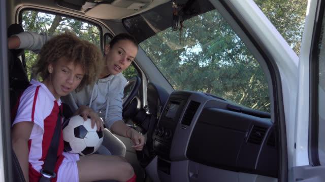 vídeos y material grabado en eventos de stock de joven madre de fútbol recoger a los niños para la práctica de fútbol en una mini van - urgencia