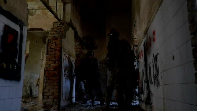 Young soldiers training for counter terrorist operation in bombarded building video