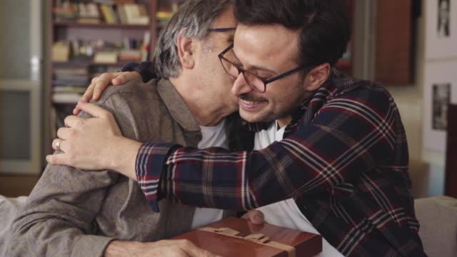 vídeos de stock, filmes e b-roll de jovem filho abraçando seu pai com amor e dando presente - dia dos pais