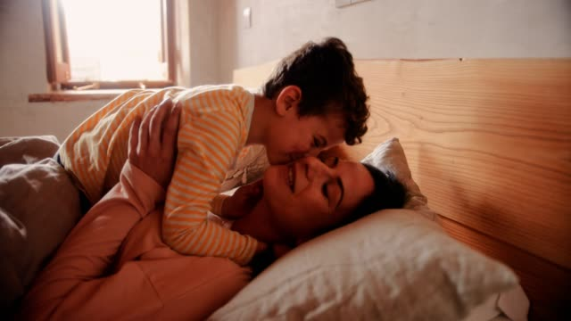 Young son kissing mother in bed in the morning video