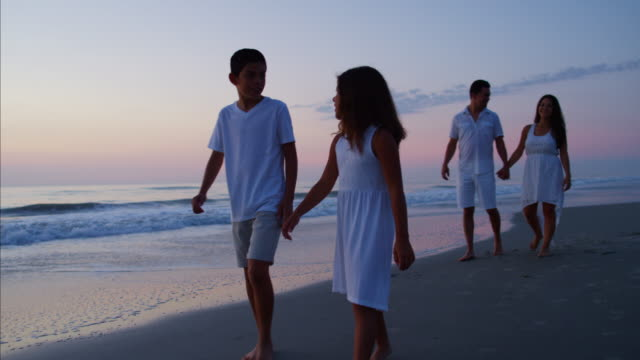 Young Spanish family enjoying beach vacation at sunrise