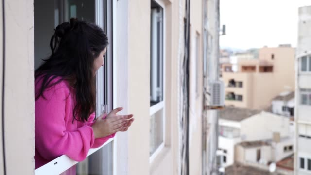 young spanish woman giving an applause to all sanitary staff from her apartment window during quarantine from covid 19 in mallorca, spain - battere le mani esprimere a gesti video stock e b–roll