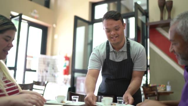 vídeos de stock e filmes b-roll de young special needs waiter serving coffee to customer in a coffee shop - capacidades diferentes