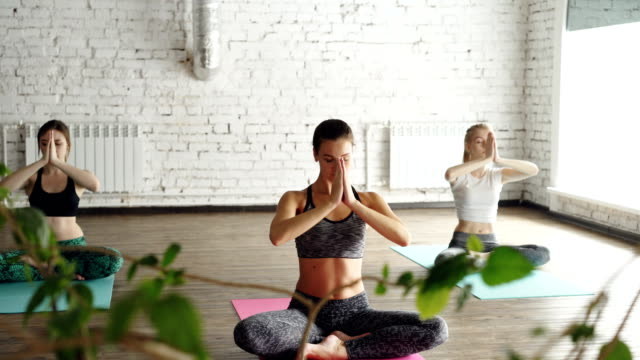 young spiritual girls are doing relaxation breating exercises in yoga studio. they are doing namaste mudra, then lowering hands on knees. relaxing self-development energy concept. - mudra video stock e b–roll