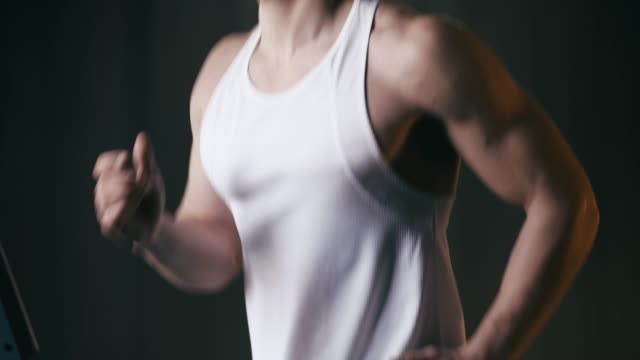 young sportive man running on treadmill in gym young sportive man running on treadmill in gym tank top stock videos & royalty-free footage