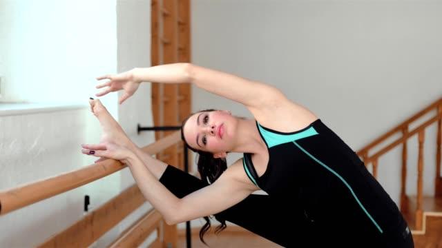 ung sportig kvinna stretching benen i ett gym. vacker flicka gör en balett-träning - balettstång bildbanksvideor och videomaterial från bakom kulisserna