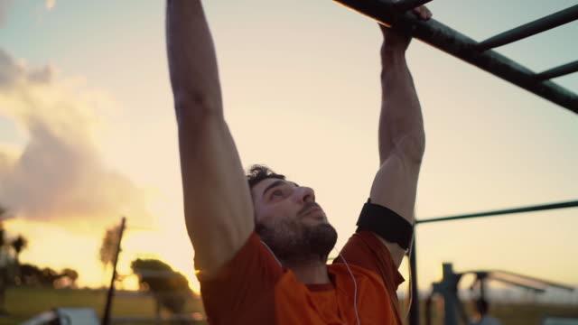 junge sportler mann mit kopfhörern in den ohren tun pull ups auf horizontalen bar auf spielplatz - turngerät mit holm stock-videos und b-roll-filmmaterial
