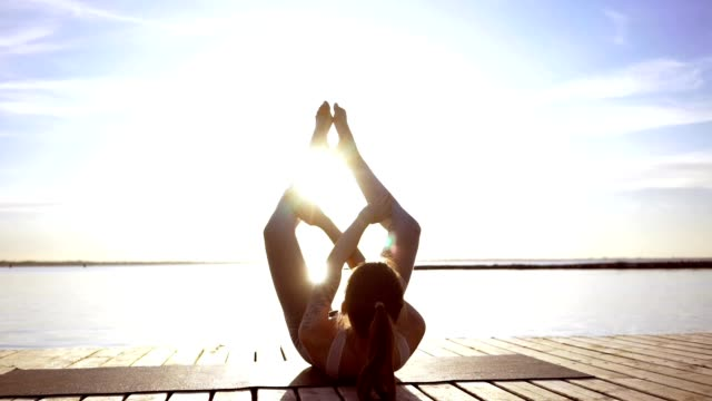 Young sports strong woman at the beach make yoga exercises video