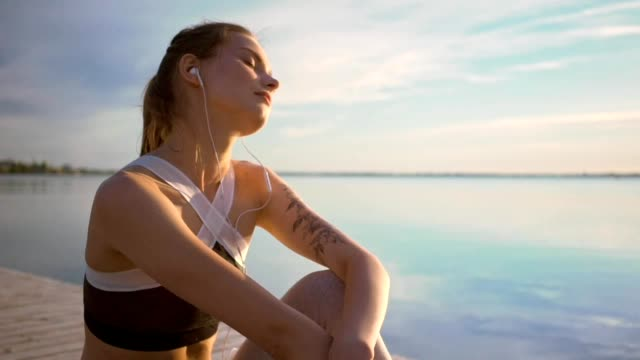 Young sports strong woman sitting at the beach listening music with earphones video