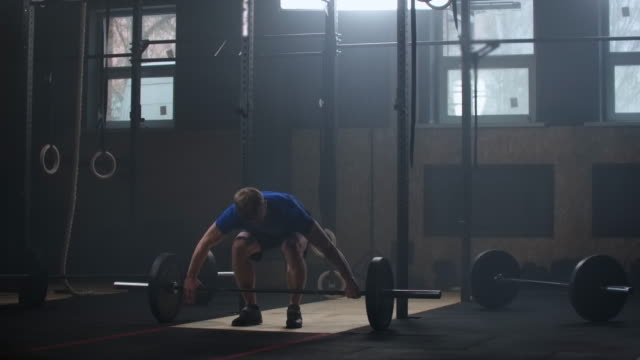 Young sportsman lifting heavy barbell. Healthy, muscular. Strong man doing barbell snatch exercise at the gym in slow motion. Sportsman on exercise mat doing situps in gym.