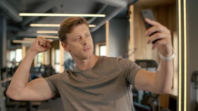 stockvideo's en b-roll-footage met jonge sportsman die selfiefoto maakt bij gymnastiek. bodybuilder die zich in sportclub bevindt - call center