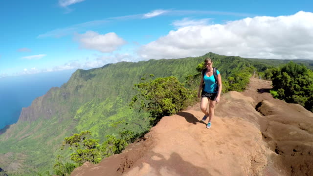 Young sportswoman walking along the high mountain path with stunning ocean view video