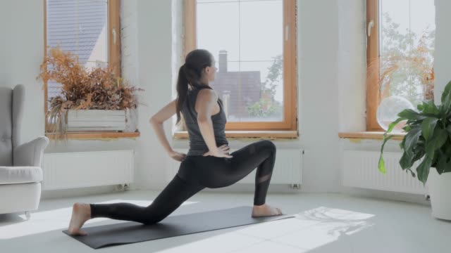 Young sporty brunette girl in sportswear does exercises in bright room at home Young fit sporty brunette girl with pigtail in gray top, black leggings does exercises on mat in bright room. Doing sports and fitness training at home. Healthy lifestyle. stretching, leaning forward bodyweight training stock videos & royalty-free footage