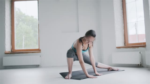 Young sporty brunette girl in sportswear does exercises in bright room at home Young fit sporty brunette girl with pigtail in blue top, gray leggings does exercises on mat in bright room. Doing sports and fitness training at home. Healthy lifestyle. stretching, leaning forward bodyweight training stock videos & royalty-free footage