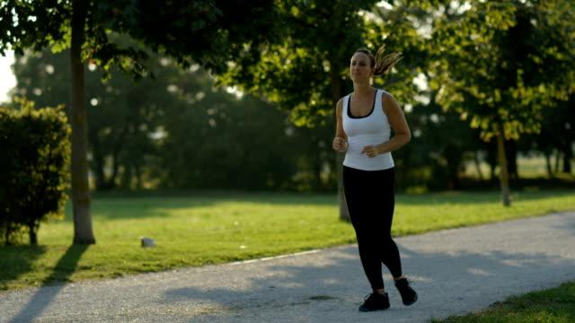 緑豊かな公園の美しい木の遊歩道で実行しているスローモーション: 若いスポーティな女の子 - 動物の身体各部点の映像素材/bロール