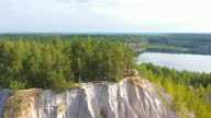 istock Young sporty guy with bicycle sitting on a bench near a mountain of rubble near a lake in the forest. Drone view of the lake in the forest 1283309524