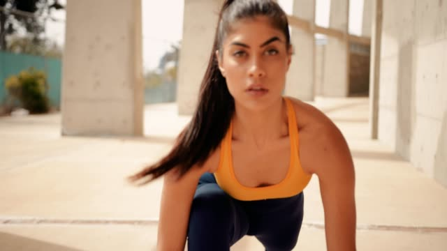 young sporty hispanic woman stretching and getting ready for running - rozgrzewka filmów i materiałów b-roll