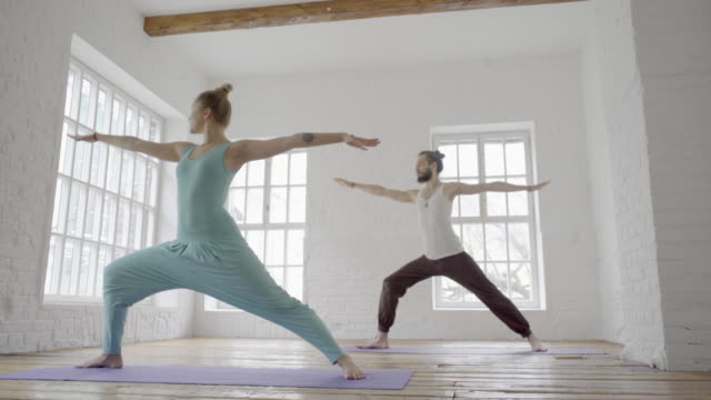 young sporty man and woman doing ashtanga yoga video