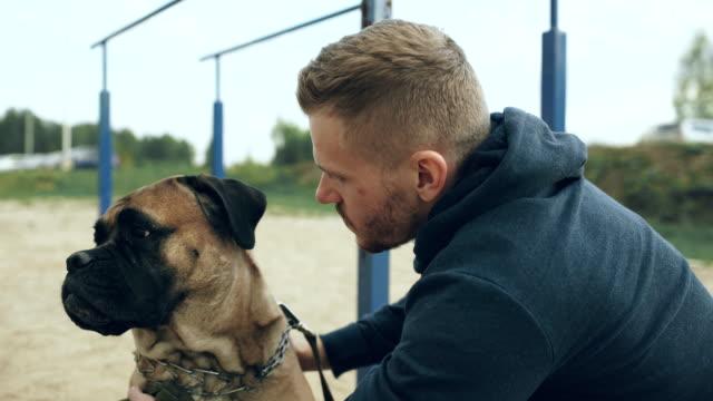 Young sporty man hug and play his bullmastiff dog outdoor at nature