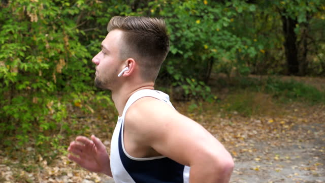 young sporty man running along trail near forest at early autumn. handsome sportsman with wireless headphones jogging outdoor. athletic guy exercising at nature. healthy active lifestyle. side view - cuffie wireless video stock e b–roll