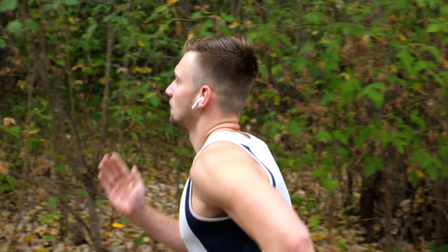 Young sporty man running along trail near forest at early autumn. Handsome sportsman with wireless headphones jogging outdoor. Athletic guy exercising at nature. Healthy active lifestyle. Side view