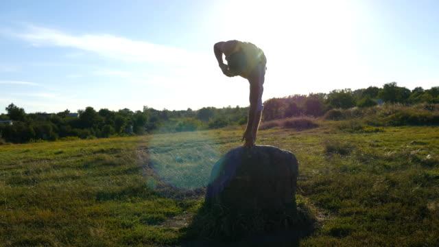 ung sportig man står på stenen vid yogaställning utomhus. yogi öva yoga flyttar och positioner i naturen. idrottsman balansera på ett ben. vackert landskap som bakgrund. hälsosam aktiv livsstil - korslagda ben bildbanksvideor och videomaterial från bakom kulisserna