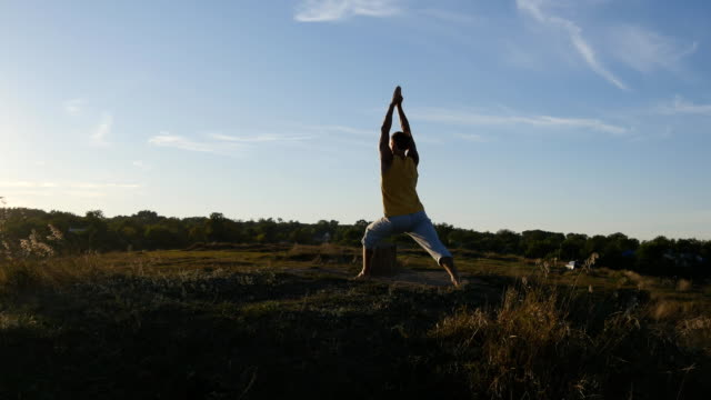 Young sporty man standing at yoga pose outdoor. Caucasian guy practicing yoga moves and positions in nature. Athlete balancing. Beautiful landscape as background. Healthy active lifestyle video