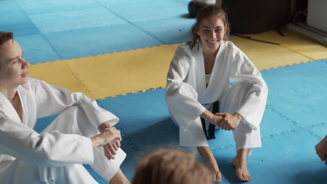 Young Sporty People Having Pleasant Talk High angle view of young Caucasian male and female martial arts fighters wearing kimonos sitting on floor in fighting center and chatting martial arts stock videos & royalty-free footage