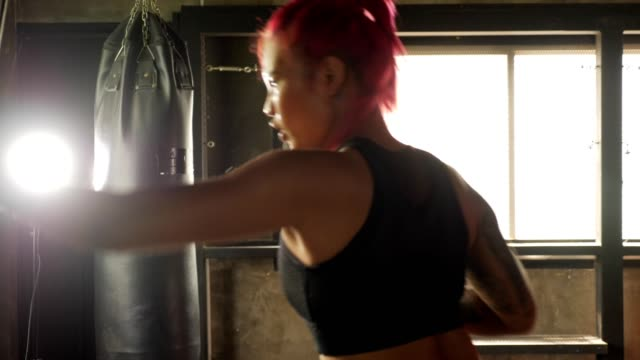 young sporty woman doing boxing training with punching bag at the gym - sacco per il pugilato video stock e b–roll