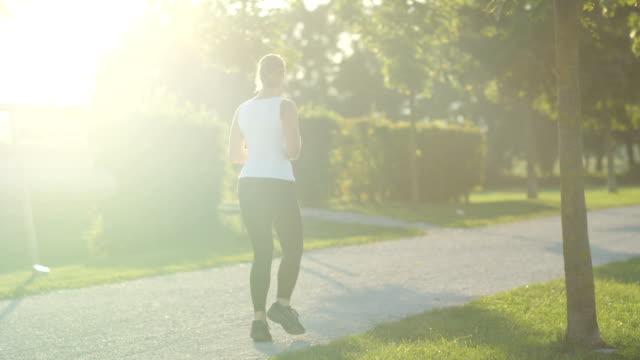 緑豊かな公園で驚くべき木の遊歩道でのジョギング スローモーション: 若いスポーティな女性 - 動物の身体各部点の映像素材/bロール