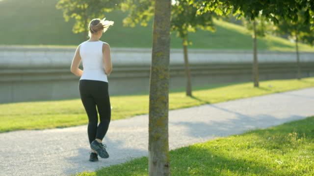 緑豊かな公園で日当たりの良い木の遊歩道でのジョギング スローモーション: 若いスポーティな女性 - 動物の身体各部点の映像素材/bロール