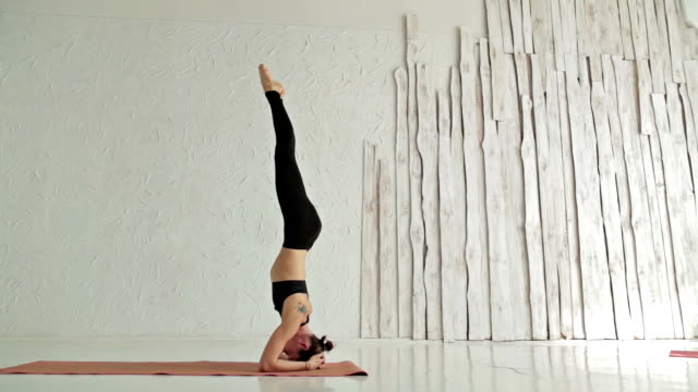Young sporty woman practicing yoga in fitness studio video