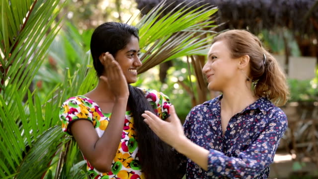 Young Sri Lankan woman chatting with a caucasian woman Young Indian - Sri Lankan woman chatting with a caucasian woman and posing to the camera sri lankan culture stock videos & royalty-free footage